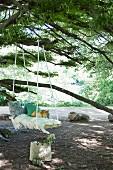 DIY-Schaukelbrett mit Kissen und Fransendecke an Baum aufgehängt