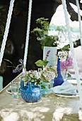 Sommerlich gedeckte Tischplatte mit Blumen im Garten