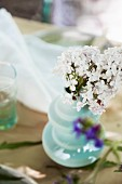 White lilac in turquoise vase in garden table