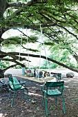 An Ast hängende DIY-Tischplatte und türkisfarbene Gartenstühle