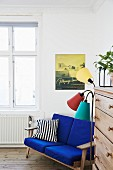 Blue-upholstered couch next to retro standard lamp and chest of drawers