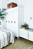 Leather suitcases on top of white lockers and sideboard in bedroom with rustic board floor