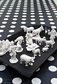 Christmas crib figurines dipped in plaster on black tray