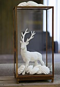 Stag figurine dipped in plaster and arranged with meringues in glass case