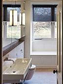 Wood-clad bathtub and screen on window in bathroom