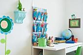 Schreibtisch und Wandutensilo im Kinderzimmer in Blau und Grün