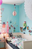 Colourful decorations on pale blue wall above bed in child's bedroom