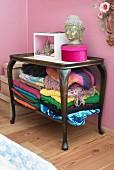 Bunte Decken und Textilien in einem alten Tischchen
