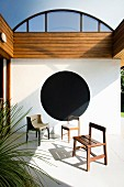 Various chairs on veranda with black circle on wall