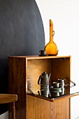 Retro-style cabinet with coffee set in fold-down cupboard against black circle on wall