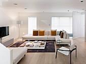 Modernes Wohnzimmer mit hellen Möbeln und Holzboden