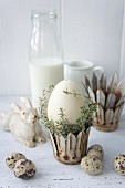 Easter egg and thyme in metal crown next to quail eggs