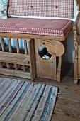 Sitzbank mit Hühnerkäfig im historischen Bauernhaus