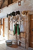 Collection of hats on coat rack made from old pitchforks and yoke