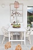 Altes Fenster über weißem Tisch und Stühlen auf der Terrasse