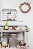 Wooden crate used as wall-mounted shelf above ornaments on potting table