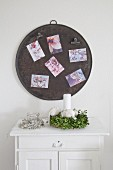 Postcards on round metal sheet used as magnetic pinboard above wreath of box
