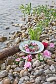 Teller mit Blumenkranz und Blüten im Kiesbett am Wasser