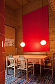 Red artwork and illuminated spherical lamps in high-ceilinged dining room in wooden house