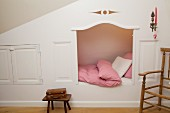 Traditional cubby bed with shutters under sloping ceiling