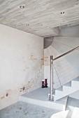 Betontreppe mit Stahlgeländer und Wandgestaltung mit Beton und Ziegelsteinen
