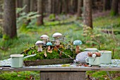 Wooden toadstools and moss on tray on picnic table in woods