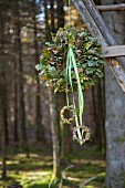 Wreath of oak leaves and ribbons hung in woods