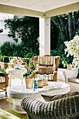 Verschiedene Korbmöbel auf einer sommerlichen Veranda