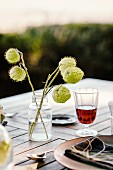 Glass of red wine and autumnal flower arrangement on table