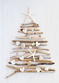Christmas tree formed from driftwood and pebbles on white surface
