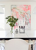 Vase and candelabra on dining table in front of abstract painting