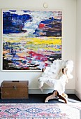 Fur blanket on old swivel chair and treasure chest below abstract artwork on wall