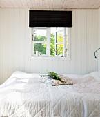 Kleines, weißes Schlafzimmer mit Fenster zum Sommergarten