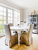 Chairs with beige loose covers around oval dining table