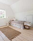 Attic bedroom in natural shades with fitted cupboard in jamb wall