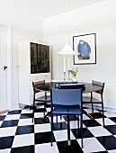 Round black table and blue chairs on black and white chequered floor
