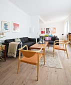 Wooden floor, black sofas and wood and leather chairs in open-plan interior of renovated period apartment