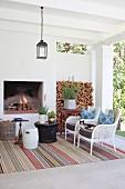 Rug, armchairs and open fireplace on comfortable veranda