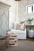 Armchair in corner of cosy living room with floral wallpaper