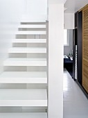 White cantilevered stairs and view of hallway