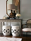 Buddha statue on console table above two stools