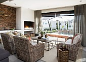 Wicker furniture, open fire and rustic stone wall in lounge with view of open-air terrace