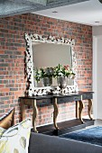 Artistic mirror leant against brick wall and flowers in silver goblet on top of console table