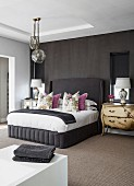 Antique chest of drawers and artistic table lamps in elegant bedroom