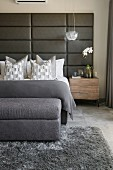 Bed with upholsered headboard in bedroom in shades of grey