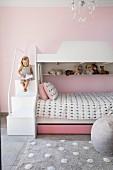 Girl sitting on steps of bunk beds in pink children's bedroom