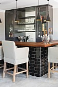 Upholstered bar stools at black and grey bar with wooden worksurface