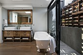 White, free-standing bathtub in front of open sliding doors leading to narrow courtyard with rustic wooden screen