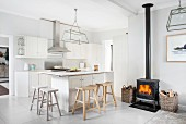 Black log-burning stove and rustic wooden bar stools at counter in white, open-plan kitchen