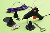 Craft utensils for Halloween decorations: glue gun, hand-made witches' hats, sweets and rubber spider